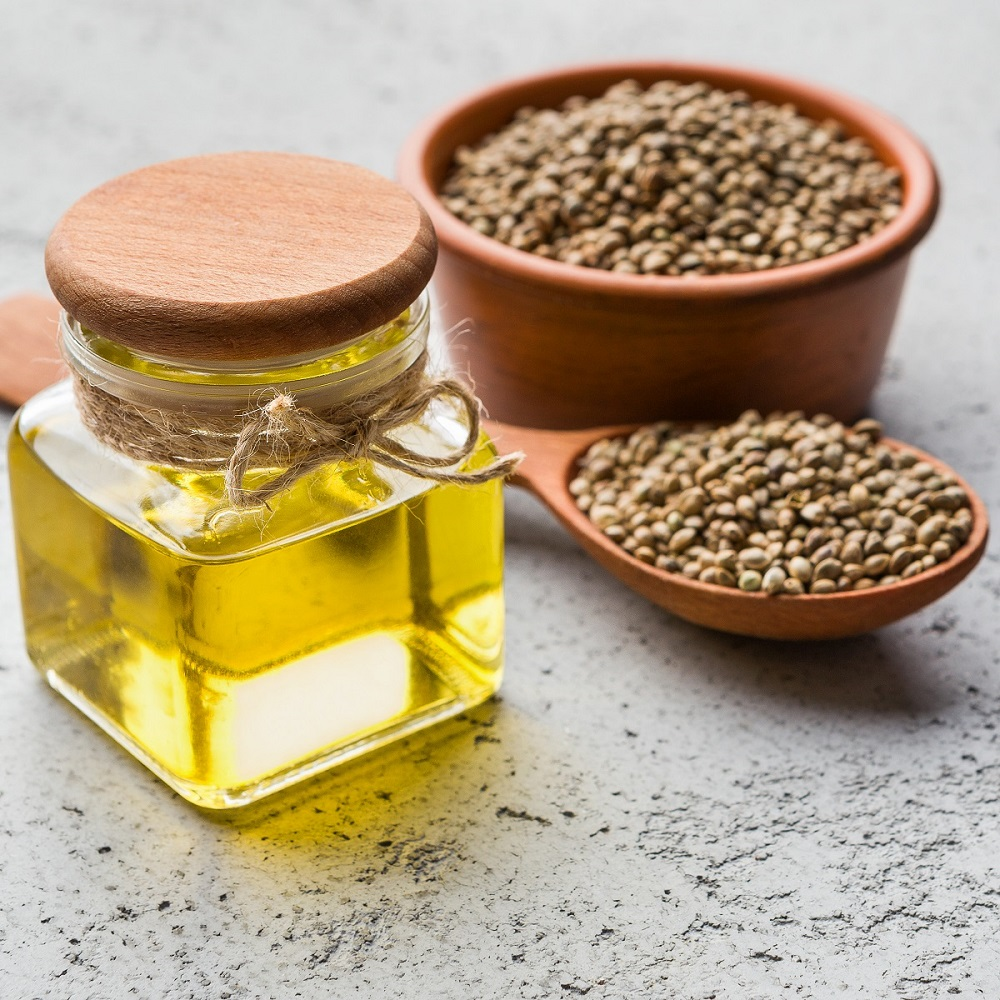 Hemp oil in bottle and hemp seeds in bowl and spoon over concrete background